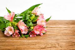 Blumenstrauß von rosa Alstroemeria auf hölzerner Platte Stockbilder