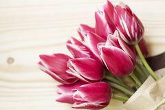Blumenstrauß von rosa Tulpen auf einem hölzernen Hintergrund Stockbilder