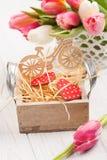Blumenstrauß von rosa Tulpen, hölzernes Fahrrad, rote Herzen Stockbilder