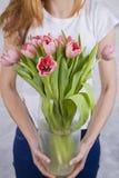 Blumenstrauß von rosa Tulpen im Großen Glasvase in den Händen von schönem Stockbild
