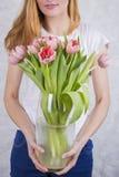 Blumenstrauß von rosa Tulpen im Großen Glasvase in den Händen von schönem Lizenzfreie Stockfotos