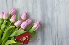 Blumenstrauß von rosa Tulpen und von rotem Herzen auf hölzernem Hintergrund Lizenzfreie Stockfotos