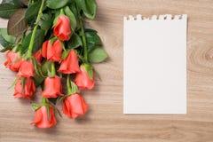 Blumenstrauß von rosaroten Rosen und von Grußkarte auf einem hölzernen Hintergrund Stockfotos