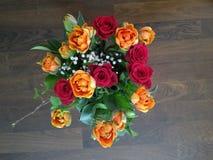 Blumenstrauß von Rosen auf Bretterboden Stockbilder