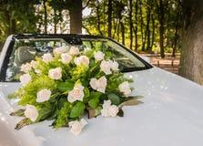 Blumenstrauß von Rosen auf dem Brautauto stockfotografie