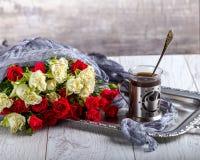 Blumenstrauß von Rosen auf dem Tisch Tasse Kaffee auf einem Behälter in der Nähe Lizenzfreie Stockfotos