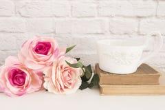 Blumenstrauß von Rosen auf einem weißen Schreibtisch, A großer Tasse Kaffee über alten Büchern, romantischer Blumenrahmenhintergr Lizenzfreies Stockfoto