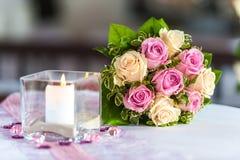 Blumenstrauß von Rosen auf Tabelle mit Kerze stockbild