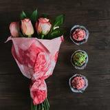 Blumenstrauß von Rosen und von kleinen Kuchen Stockbilder