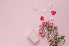Blumenstrauß von Rosen, von Geschenkbox und von Herzen auf einem rosa Hintergrund Spac Stockfoto