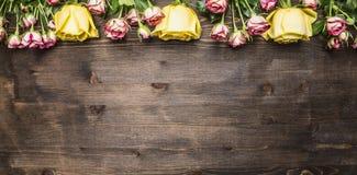 Blumenstrauß von Rosen von verschiedenen Blumensorten, von gelben Rosen und von rosa Strauchrosegrenze, Platztext auf hölzernem r Lizenzfreie Stockbilder