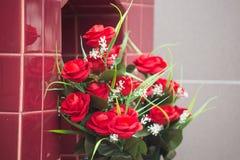 Blumenstrauß von roten Rosen auf dem Grab stockfoto