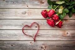 Blumenstrauß von roten Rosen auf hölzernem Hintergrund mit Herzen vom Band Lizenzfreies Stockfoto
