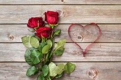 Blumenstrauß von roten Rosen auf hölzernem Hintergrund mit Herzen vom Band Stockbilder