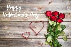 Blumenstrauß von roten Rosen auf hölzernem Hintergrund mit Herzen vom Band Stockfotos