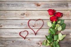 Blumenstrauß von roten Rosen auf hölzernem Hintergrund mit Herzen vom Band Lizenzfreies Stockbild