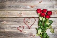 Blumenstrauß von roten Rosen auf hölzernem Hintergrund mit Herzen vom Band Stockfotografie