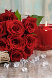 Blumenstrauß von roten Rosen auf Holztisch Stockfotos