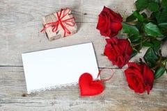 Blumenstrauß von roten Rosen mit rotem Herzen und Geschenkbox auf hölzernem Hintergrund Lizenzfreie Stockfotos