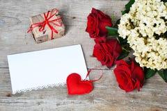 Blumenstrauß von roten Rosen mit rotem Herzen und Geschenkbox auf hölzernem Hintergrund Lizenzfreie Stockfotografie