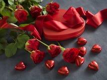 Blumenstrauß von roten Rosen und von Band mit rotem Präsentkarton Stockfoto