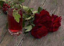 Blumenstrauß von roten Rosen und von Glas mit rotem Getränk Stockfoto