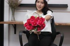 Blumenstrauß von roten Rosen wird auf Händen der attraktiven jungen Asiatin im Büro an Valentinsgruß ` s Tag gehalten Liebes- und Stockfotografie