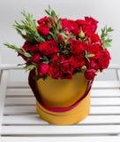 Blumenstrauß von roten Sprayrosen und -eukalyptus in einem Kasten auf Holztisch Kopieren Sie Platz Leerzeichen für Text stockfotografie
