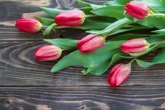 Blumenstrauß von roten Tulpen auf der Draufsicht des Holztischs stockbild