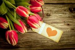 Blumenstrauß von roten Tulpen mit einem roten Herzgeschenktag Stockfotos
