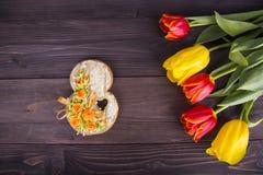 Blumenstrauß von roten und gelben Tulpen mit Stelle 8 auf hölzernem backgrou Stockbilder