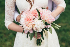 Blumenstrauß von Sahnepfingstrosen in den Händen der Braut Stockfoto