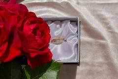 Blumenstrauß von schönen Blumen der roten Rosen und von glänzenden Eheringen auf beige Atlassatinhintergrund lizenzfreies stockfoto