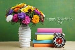 Blumenstrauß von schönen Blumen und ein Stapel Bücher Lizenzfreies Stockbild