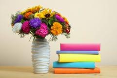 Blumenstrauß von schönen Blumen und ein Stapel Bücher Lizenzfreie Stockfotos