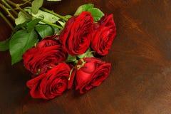 Blumenstrauß von schönen roten Rosen auf einer dunklen hölzernen Hintergrundnahaufnahme Lizenzfreies Stockfoto