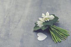 Blumenstrauß von Schneeglöckchen auf grauem Steinhintergrund mit Kopienraum f Lizenzfreies Stockbild