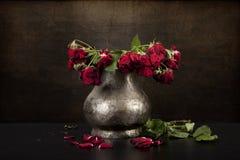 Blumenstrauß von toten roten Rosen im Zinnvase, Schmutzhintergrund Stockfotos