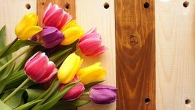 Blumenstrauß von Tulpen über Platten auf Holztisch Lizenzfreie Stockfotos