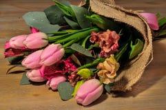 Blumenstrauß von Tulpen auf dem Tisch mit Stockfotografie