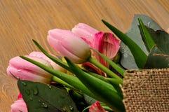 Blumenstrauß von Tulpen auf dem Tisch mit einer Anmerkung Stockfotos