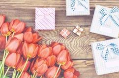 Blumenstrauß von Tulpen auf Holztisch mit Geschenken Stockfoto
