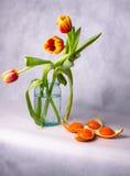 Blumenstrauß von Tulpen in einem Glasgefäß und in orange Kerzen Lizenzfreies Stockbild