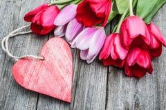 Blumenstrauß von Tulpen mit einem Empty tag und einem roten Herzen Lizenzfreies Stockfoto