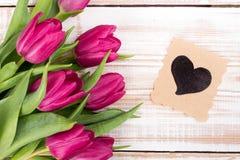 Blumenstrauß von Tulpen und von dekorativer Karte mit Herzen Lizenzfreie Stockfotografie