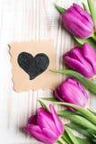 Blumenstrauß von Tulpen und von dekorativer Karte mit Herzen Stockbilder