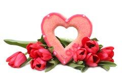 Blumenstrauß von Tulpen und von Zuckerherzen auf einem weißen Hintergrund Lizenzfreie Stockfotos