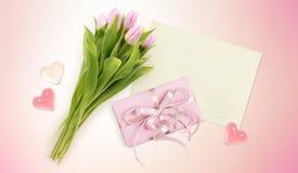 Blumenstrauß von Tulpen, von Karte, von Herzen und von Kastengeschenk auf Rosa Lizenzfreies Stockbild