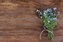 Blumenstrauß von Vergissmeinnichten auf altem hölzernem Hintergrund Stockfotos