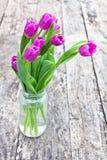 Blumenstrauß von violetten Tulpen auf der Eichenbrauntabelle in einem Klarglasglas Lizenzfreies Stockbild